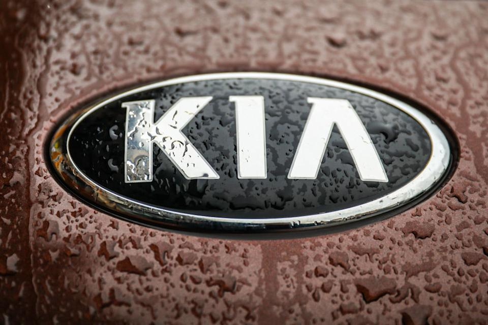 A Kia car emblem is covered with raindrops.