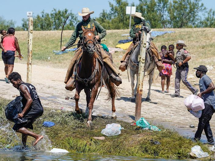 United States Border Patrol agents on horseback try to stop Haitian migrants from entering an encampment on the banks of the Rio Grande near the Acuna Del Rio International Bridge in Del Rio, Texas on September 19, 2021. - US law enforcement are attempting to close off crossing points along the Rio Grande river where migrants cross to get food and water, which is scarce in the encampment. The United States said Saturday it would ramp up deportation flights for thousands of migrants who flooded into the Texas border city of Del Rio, as authorities scramble to alleviate a burgeoning crisis for President Joe Biden's administration.