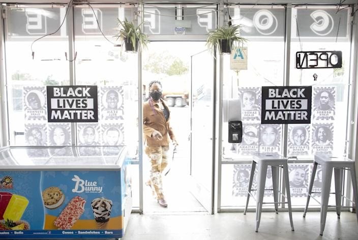 A woman walks through the door of a shop with Black Lives Matter signs in the window