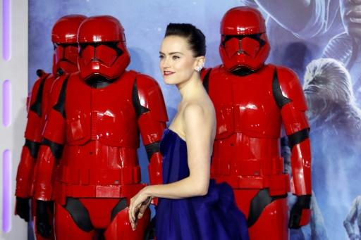 """British actor Daisy Ridley poses with stormtroopers upon arrival for the European premiere of Disney's """"Star Wars: The Rise of Skywalker"""" in London on December 18, 2019"""