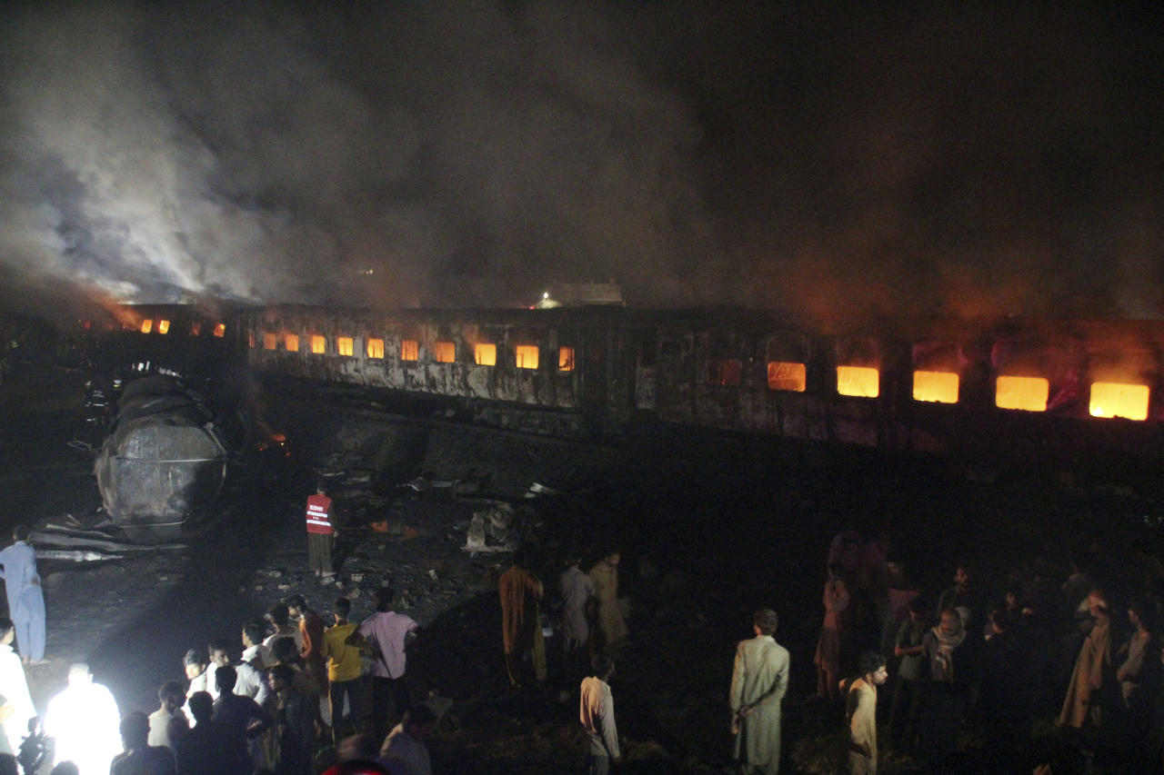 People look at a burning passenger train in Shaikhupura, near Lahore, Pakistan, early Tuesday, March 28, 2017. Authorities in Pakistan say a passenger train has collided with an oil tanker truck, killing at least one person and injuring others. (AP Photo/K.M. Chaudary)
