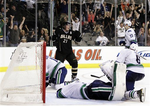 Fans react along with Dallas Stars' Loui Eriksson (21), of Sweden, after Eriksson scored the game-winning goal against Vancouver Canucks goalie Roberto Luongo, bottom, in overtime of an NHL hockey game, Sunday, Feb. 26, 2012, in Dallas. The Stars won 3-2. (AP Photo/Tony Gutierrez)
