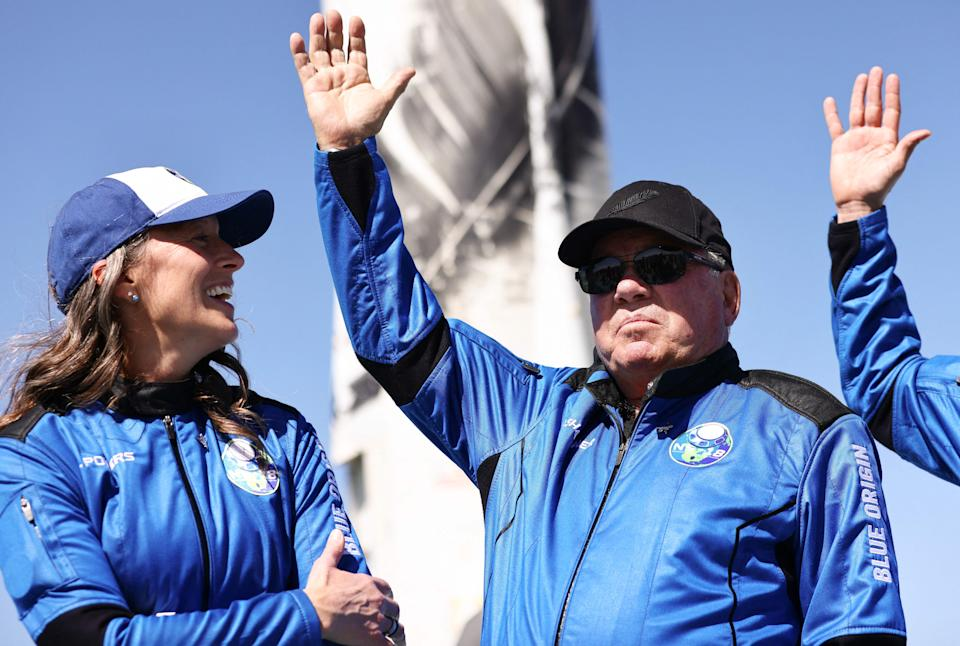 VAN HORN, TEXAS - OCTOBER 13: Blue Origins vice president of mission and flight operations Audrey Powers (L) looks on as Star Trek actor William Shatner waves during a media availability on the landing pad of Blue Origin's New Shepard after they flew into space on October 13, 2021 near Van Horn, Texas. Shatner became the oldest person to fly into space on the ten minute flight. They flew aboard mission NS-18, the second human spaceflight for the company which is owned by Amazon founder Jeff Bezos.   Mario Tama/Getty Images/AFP / AFP / GETTY IMAGES NORTH AMERICA / MARIO TAMA