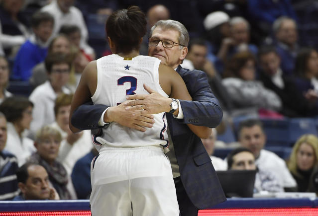 Connecticut head coach Geno Auriemma hugs Connecticut's Megan Walker in the second half of an NCAA college basketball game, Sunday, Dec. 8, 2019, in Storrs, Conn. (AP Photo/Jessica Hill)