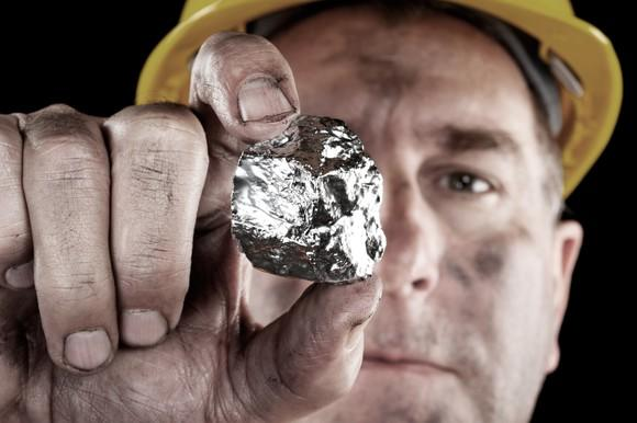 A miner holding a silver nugget