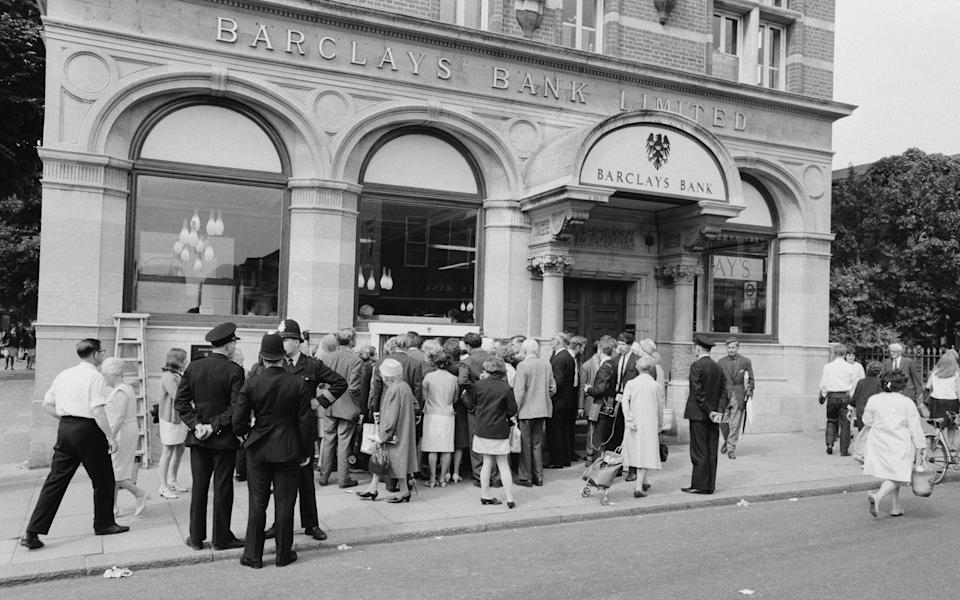 The Worlds First ATM, Cash Machine is unveiled at Barclays Bank, in Enfield, Middlesex, just North of London, 27th June 1967. Picture shows the crowd of local shoppers and onlookers, seeing the worlds first ATM work for the first time. (Photo by Tom King/Mirrorpix/Getty Images) - Getty