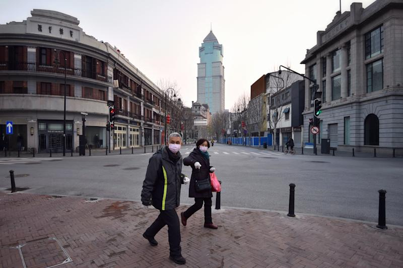 WUHAN, CHINA - FEBRUARY 21 2020: Masked people walk in the empty street due to the lockdown to curb the COVID epidemic in Wuhan in central China's Hubei province Friday, Feb. 21, 2020.- PHOTOGRAPH BY Feature China / Barcroft Studios / Future Publishing (Photo credit should read Feature China/Barcroft Media via Getty Images)