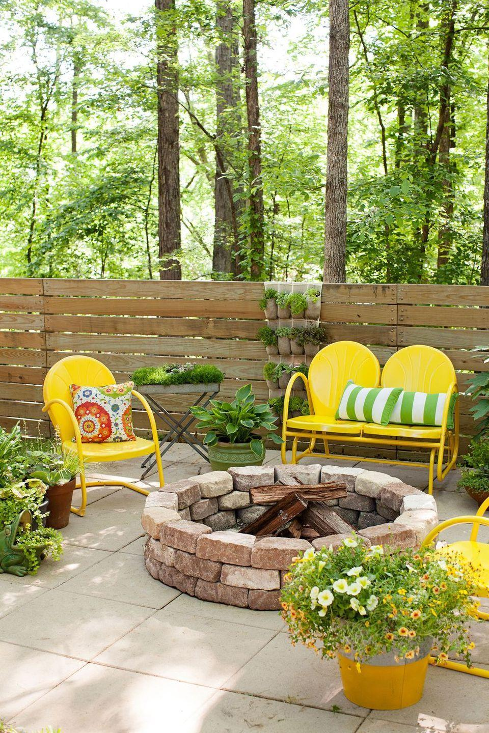 <p>Stack curved paving stones in a circle to create a statement-worthy fire pit. To make the space more inviting, scatter some metal chairs and potted plants nearby (but not too close to the fire, of course). </p>