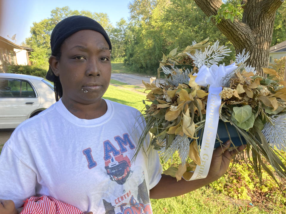 Ericka Lotts holds a bouquet from her son's funeral in this photo taken Friday, Sept. 17, 2021, at her home in Ferguson, Missouri. Martin died of a gunshot wound in rural Missouri in April. Though investigators initially called it a suicide, a coroner's inquest jury ruled that Martin died of violence.(AP Photo by Jim Salter)