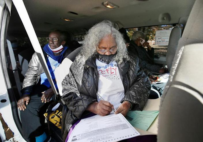 Jean Ward, 76, fills out her ballot on Tuesday, Nov. 3, 2020 in Richmond, Va.  A felony record from when she was in her 30s meant she lost the right to vote years ago. After working hard to have her voting rights restored, Ward boarded a van along with other seniors residents of Highland Park Senior Apartments to cast her ballot at the Engine 15 precinct.  (James H Wallace/Richmond Times-Dispatch via AP)