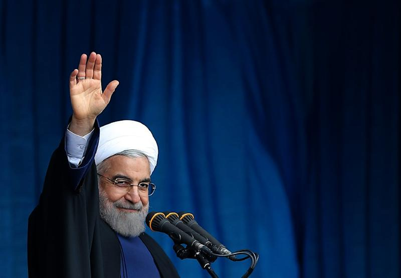 A photo provided by the office of Iranian President Hassan Rouhani shows him waving to the crowd during a public speech in the religious Shiite Muslim city of Qom, February 25, 2015