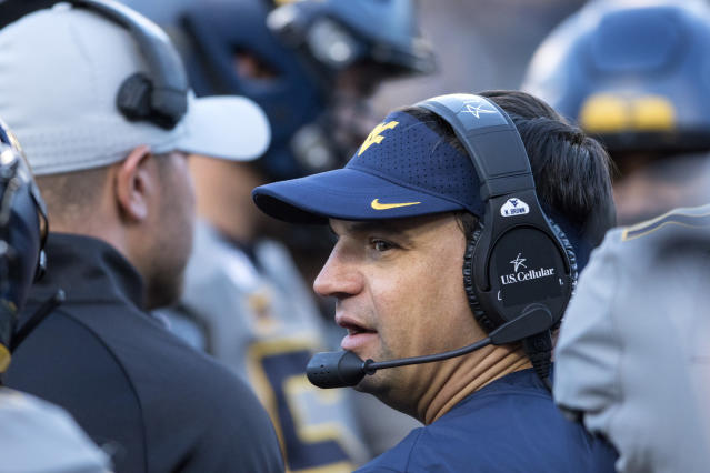 West Virginia head coach Neal Brown speaks with members of his staff during the second half of an NCAA college football game against Iowa State, Saturday, Oct. 12, 2019, in Morgantown, W.Va. (AP Photo/Raymond Thompson)