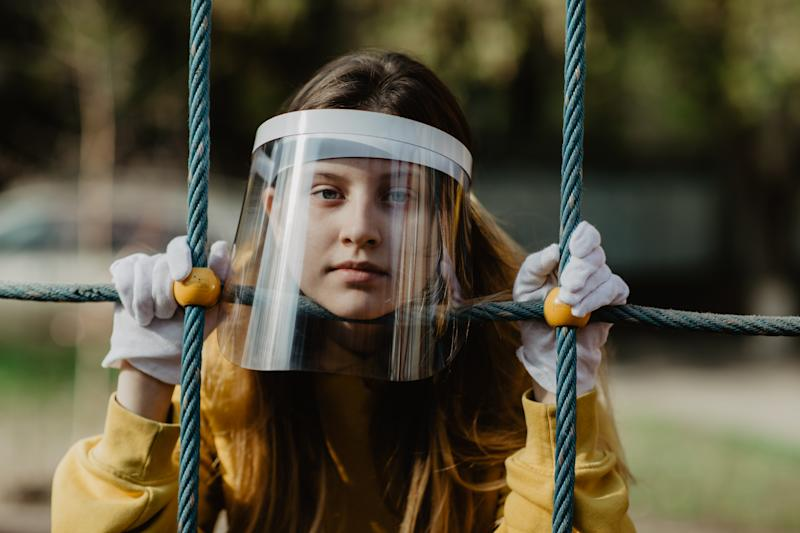 Young woman wearing face shield hiding behind the climbing wall. Nicely fits for book cover
