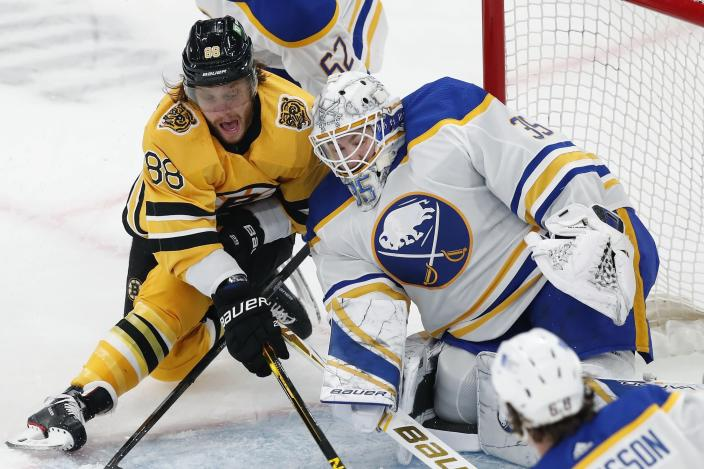 Boston Bruins' David Pastrnak (88) tries to get a shot on Buffalo Sabres' Linus Ullmark (35) during the first period of an NHL hockey game, Saturday, March 27, 2021, in Boston. (AP Photo/Michael Dwyer)