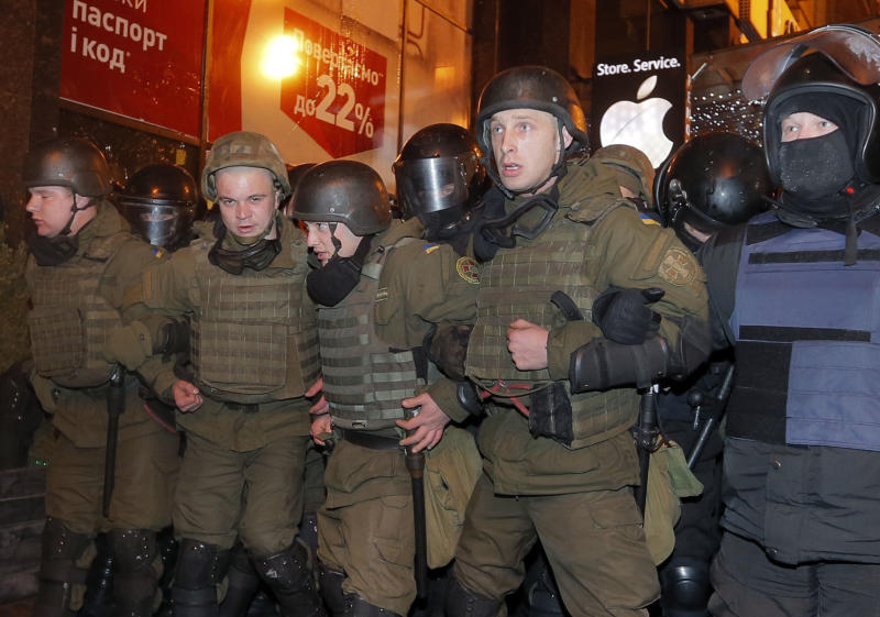Riot police stand block protesters from reaching the front of an Alfa bank office in central Kiev, Ukraine, Tuesday, March 14, 2017. Activists and supporters of Ukrainian nationalist groups are demanding the closure of all banks associated with Russia in Ukraine. (AP Photo/Efrem Lukatsky)