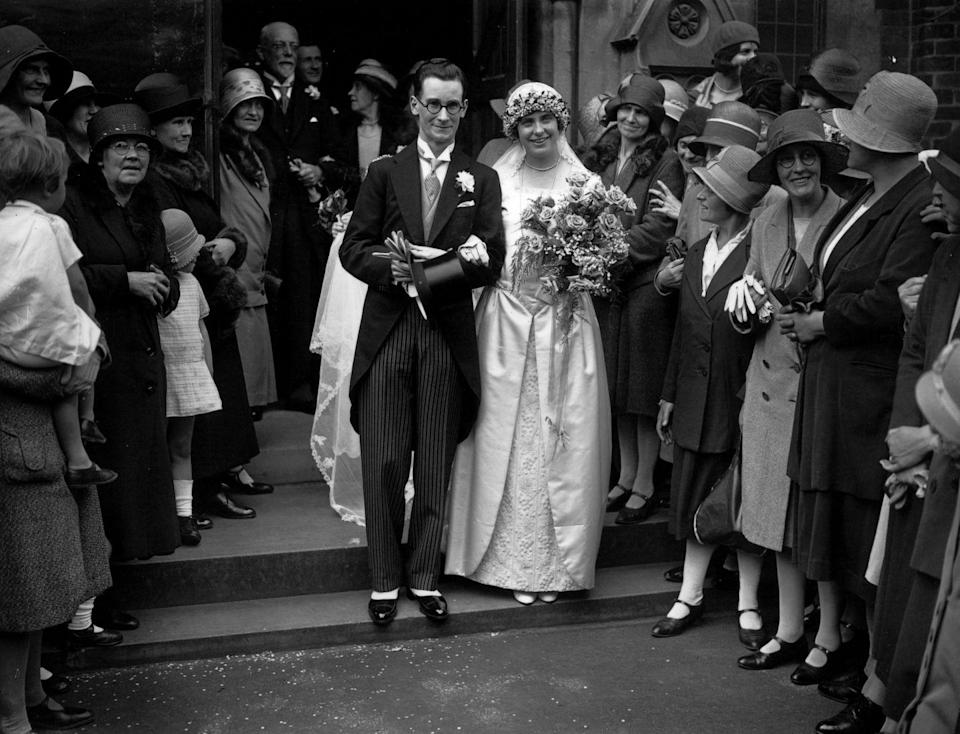 <p>This couple exited the church wearing a dapper ensemble (for the 1930s, at least), including the bride's floral halo and groom's pinstripe tuxedo. </p>