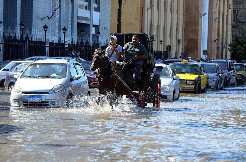 Egyptian men ride a horse carriage in a flooded street in Egypt's northern coastal city of Alexandria, following heavy rains, on October 25, 2015