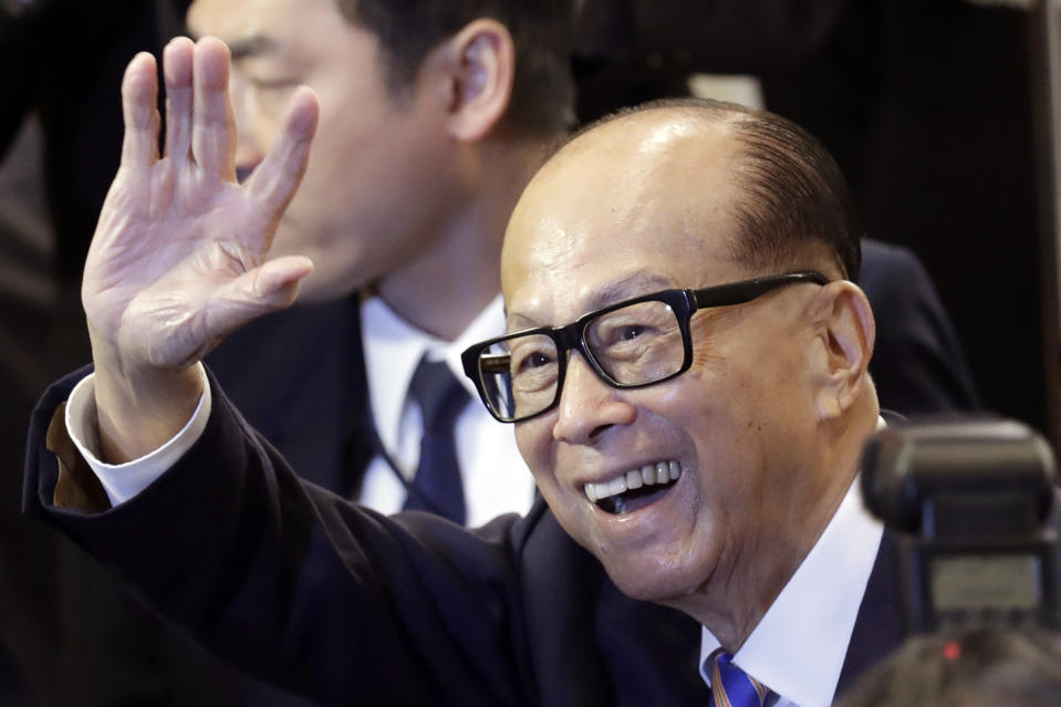 Hong Kong billionaire Li Ka-shing, chairman of CK Hutchison Holdings company, waves after a press conference to announce the company's annual results in Hong Kong, Friday, March 16, 2018. Li said Friday he is retiring as chairman of his sprawling conglomerate and handing control to his eldest son. (AP Photo/Kin Cheung)