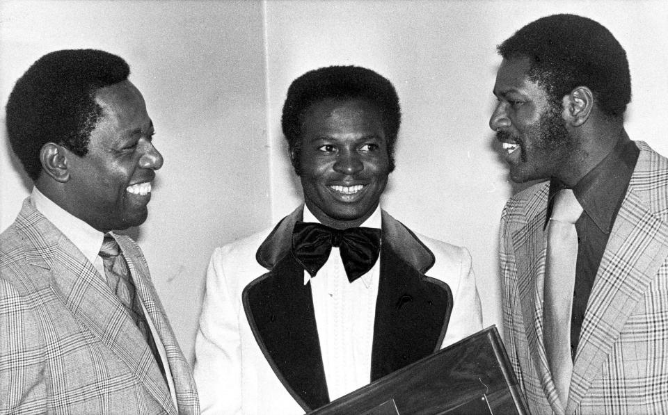 FILE - In this Jan. 28, 1975, file photo, three of the tops in baseball, from left, Hank Aaron, Lou Brock and Bob Gibson talk at an event where they were honored by St. Louis baseball writers in St. Louis. Aaron was honoroed for his 733 home runs and breaking Babe Ruth's record; Brock for his 118 stolen bases in one season and Bob Gibson for passing the National League strikeout record. In the 1970s, players of color finally stepped into an unfettered spotlight, the reserve clause ended, free agency began and the players' union found its voice. (AP Photo/File)