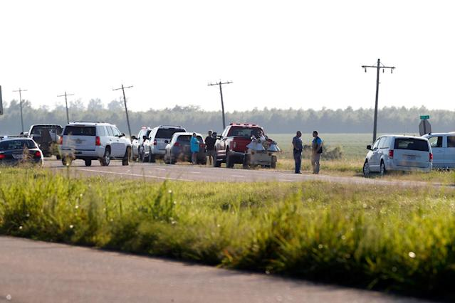 <p>Emergency personnel stand along U.S. Highway 82 after a military transport plane crashed into a field near Itta Bena, Miss., on the western edge of Leflore County, Monday, July 10, 2017. (Photo: Andy Lo/AP) </p>