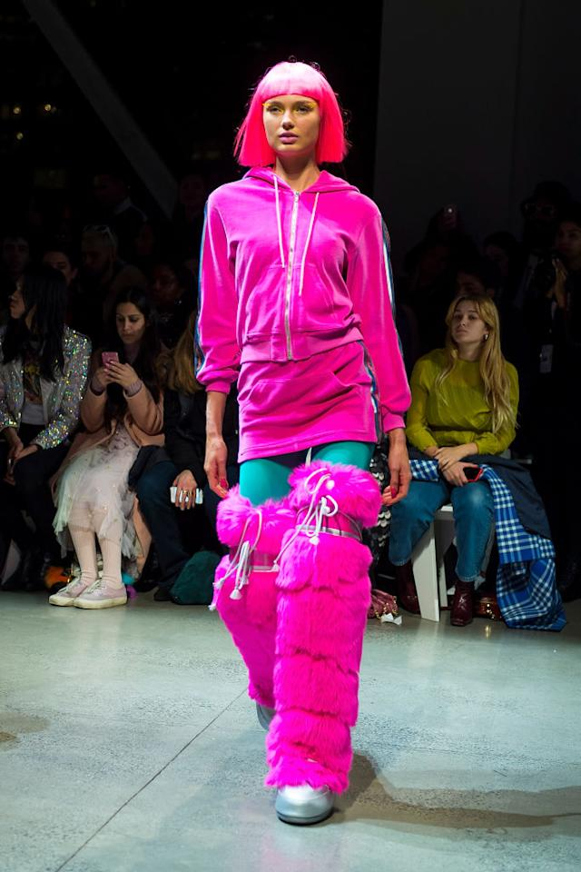 <p>Model wears a pink hoodie, skirt, and thigh-high furry moon boots at Jeremy Scott's Fall 2018 show. (Photo: Getty) </p>