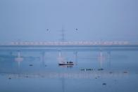 People ride a boat across Yamuna river as a metro train is seen in the background in New Delhi, India