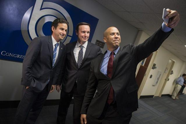 From left, Sen. Brian Schatz, D-Hawaii, Sen. Chris Murphy, D-Conn., and Sen. Cory Booker, D-N.J., take a selfie before meeting with CBO Director Keith Hall, June 20, 2017. (Photo: Tom Williams/CQ Roll Call)