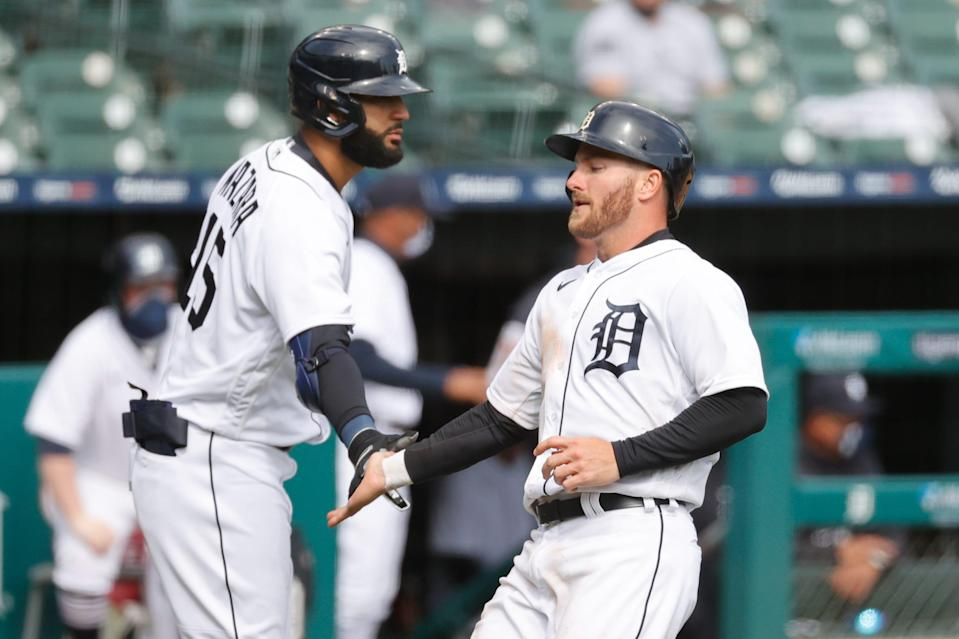 Detroit Tigers left fielder Robbie Grossman, right, receives congratulations from right fielder Nomar Mazara after scoring in the seventh inning against the Cleveland Indians at Comerica Park, Saturday, April 3, 2021.
