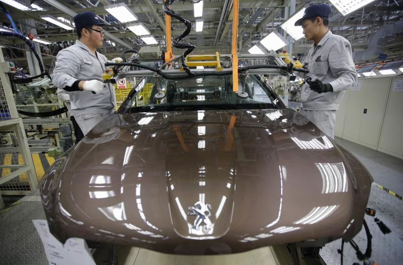 Employees work at a production line of a Dongfeng Peugeot Citroen Automobile factory in Wuhan