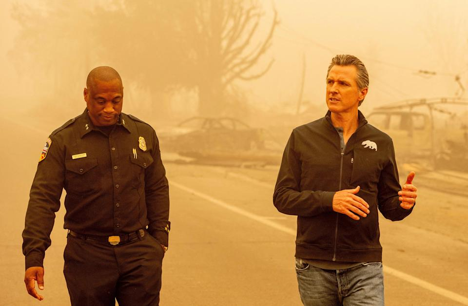 Gavin Newsom walks with Assistant Region Chief for Cal Fire Curtis Brown in downtown Greenville, California on August 7, 2021 (AFP via Getty Images)