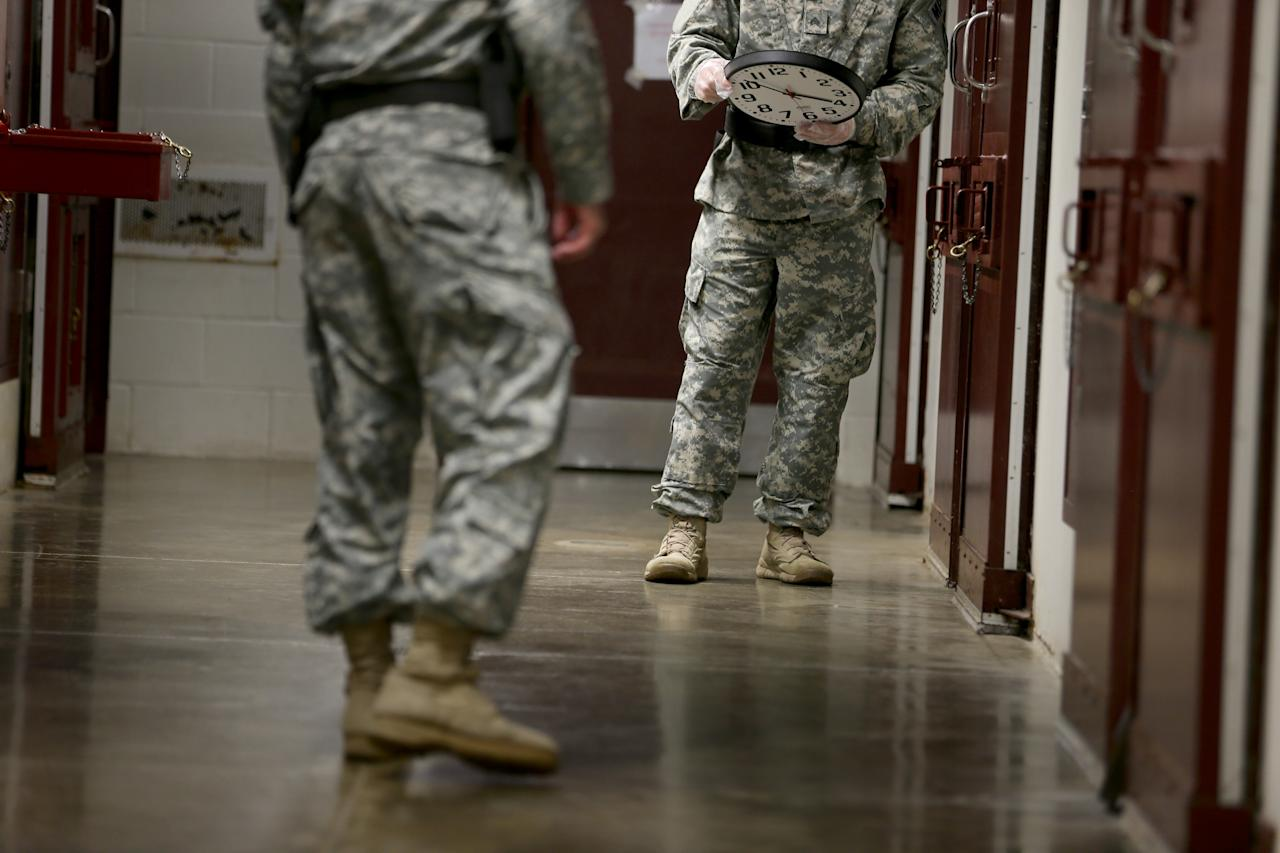 GUANTANAMO BAY, CUBA - JUNE 26: (EDITORS NOTE: Image has been reviewed by the U.S. Military prior to transmission.) U.S. Army Military Police walk through a cell block during morning prayer at Camp V in the U.S. military prison for 'enemy combatants' on June 26, 2013 in Guantanamo Bay, Cuba. President Barack Obama has recently spoken again about closing the prison which has been used to hold prisoners from the invasion of Afghanistan and the war on terror since early 2002. (Photo by Joe Raedle/Getty Images)