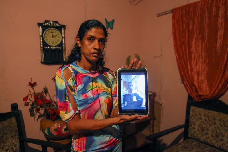 Wife of Giovanni Urbaneja poses with a photo of her husband at their home in San Jose de Guanipa