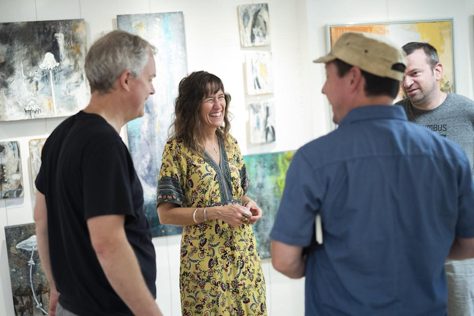 Kelly Reichert, artist and owner of 3060 Gallery, chats with other business tenents who work nearby during the Hilltop 3060 Art Brunch Saturday.