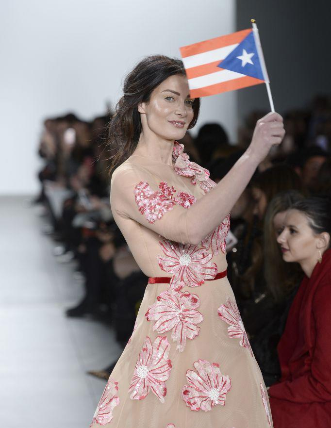 <p>Dayanara Torres walks the Stella Nolasco runway show carrying a Puerto Rican flag. (Photo: Getty Images) </p>