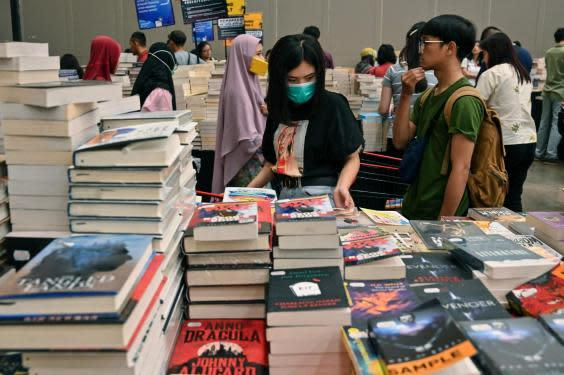 Visitors, wearing a facemasks as a preventive measure against the coronavirus, browse for books during the Big Bad Wolf Books book fair in Jakarta on 8 March 2020. (ADEK BERRY/AFP via Getty Images)