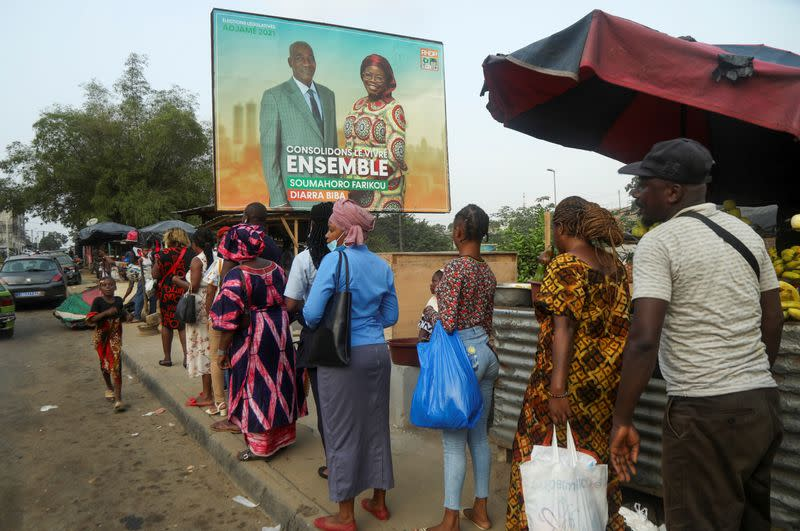 People stand in line under a campaign billboard showing the candidats of the ruling coalition party, the Rally of Houphouetists for Democracy and Peace (RHDP) ahead of the legislative election in Abidjan