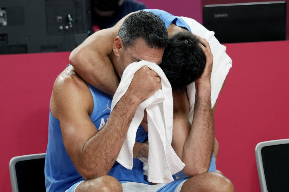 Argentina's Luis Scola (4) is hugged by teammate Facundo Campazzo as he receives an emotional standing ovation from his team, Australia players, and others in attendance when he was pulled from the game in the final moments of a men's basketball quarterfinal round game at the 2020 Summer Olympics, Tuesday, Aug. 3, 2021, in Saitama, Japan. (AP Photo/Eric Gay)