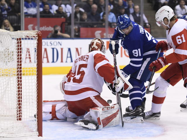 Toronto Maple Leafs center John Tavares (91) is stopped by Detroit Red Wings goaltender Jonathan Bernier (45) as Red Wings center Jacob de la Rose (61) moves in during the first period of an NHL hockey game Thursday, Dec 6, 2018, in Toronto. (Nathan Denette/The Canadian Press via AP)
