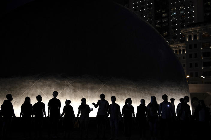 Protesters wear mask and link their hands forming a human chain during a protest in Hong Kong, Friday, Oct. 18, 2019. Hong Kong pro-democracy protesters are donning cartoon/superheroes masks as they formed a human chain across the semiautonomous Chinese city, in defiance of a government ban on face coverings. (AP Photo/Felipe Dana)
