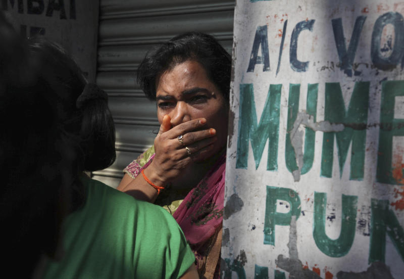 A relative of a passenger wails outside the office of a private bus operator, Jabbar Travels in Hyderabad, Andhra Pradesh state, India, Wednesday, Oct. 30, 2013 after their bus crashed into a highway barrier and erupted in flames early Wednesday. According to officials, many of the passengers were burned alive in the inferno in the accident. (AP Photo/Mahesh Kumar A.)