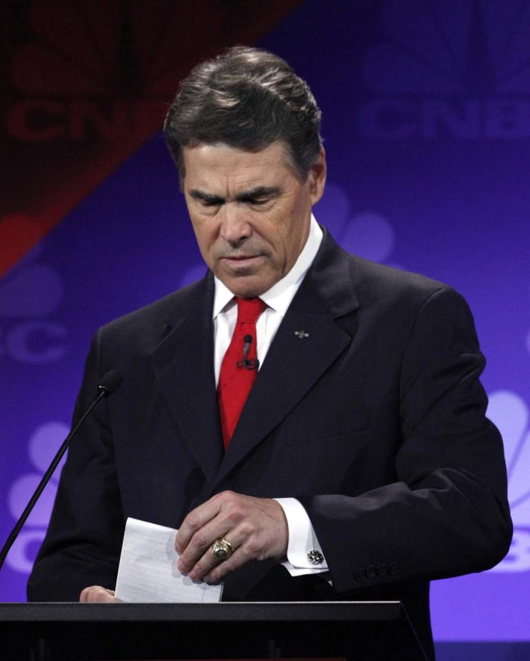 "FILE - In this Nov. 9, 2011 file photo, then-Republican presidential candidate Texas Gov. Rick Perry looks at his notes during a Republican Presidential Debate at Oakland University in Auburn Hills, Mich. The Republican primary campaign is already fading into memory. Remember Herman Cain's 9-9-9 tax plan? Newt Gingrich's ""moon base"" proposal? Or Rick Perry's ""oops"" moment _ when he couldn't recall that third federal agency he wanted to eliminate?  (AP Photo/Paul Sancya, File)"
