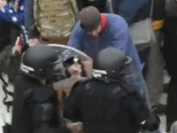 A screenshot from footage of police attempting to halt a rioter outside the Capitol, who the FBI believes is Landon Copeland.