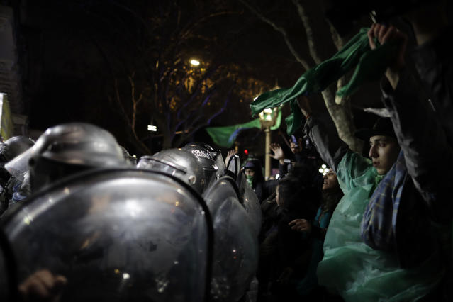 <p>Pro-choice activists stand with their arms up before police, outside Congress where clashes broke out after activists learned lawmakers voted against a bill that would have legalized elective abortion in the first 14 weeks of pregnancy, in Buenos Aires, Argentina, early Thursday, Aug. 9, 2018. (Photo: Natacha Pisarenko/AP) </p>