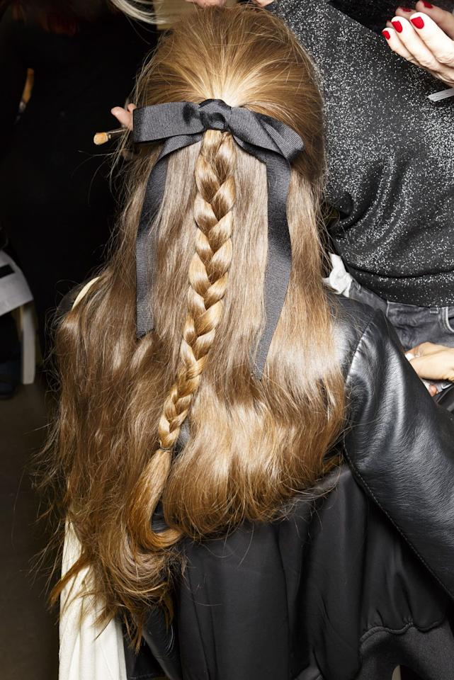 <p>Give a classic half-up half-down 'do a twist with a plait and a black ribbon.</p>