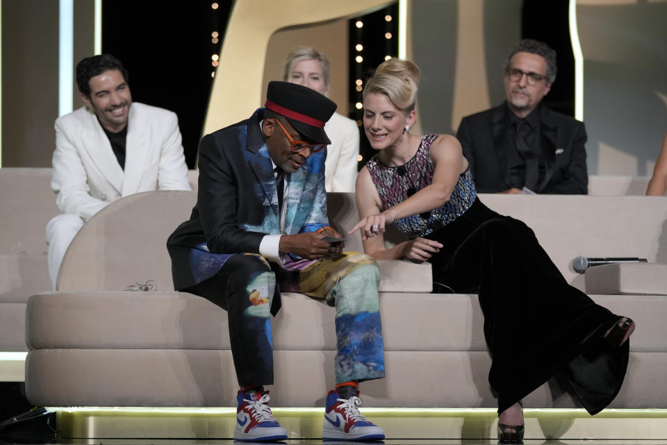 Jury president Spike Lee, bottom left, almost announces 'Titane' as the winner of the Palme d'Or for the second time as fellow jury members Tahar Rahim, from back left, Jessica Hausner, Kleber Mendonca Filho and Melanie Laurent, bottom right, look on during the awards ceremony at the 74th international film festival, Cannes, southern France, Saturday, July 17, 2021. (AP Photo/Vadim Ghirda)