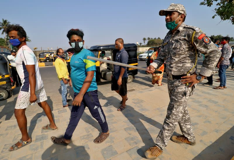 A policeman asks people to leave Juhu beach to prevent public gatherings during Holi festival in Mumbai