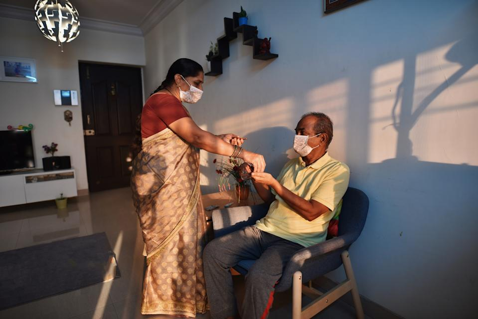 Senior woman wearing medical mask giving medicine to husband