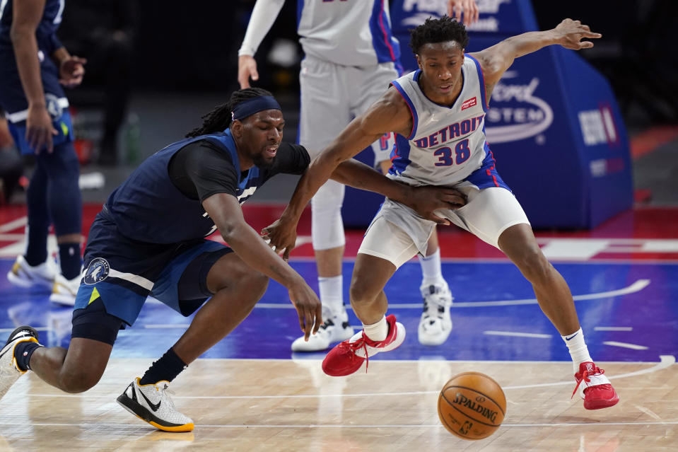 Minnesota Timberwolves center Naz Reid, left, and Detroit Pistons guard Saben Lee (38) chase the loose ball during the second half of an NBA basketball game, Tuesday, May 11, 2021, in Detroit. (AP Photo/Carlos Osorio)