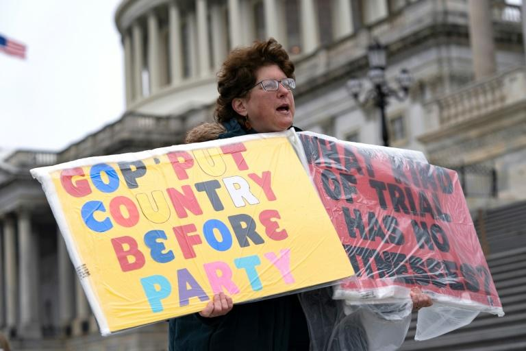 A demonstrator stands outside the US Capitol as White House lawyers began their defense of President Donald Trump at his Senate impeachment trial (AFP Photo/Alex Edelman)