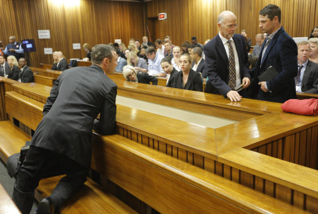 Oscar Pistorius, left, in the dock turns back to speak with his uncle, Arnold Pistorius, standing at left, and his brother Carl, standing at right, on the second day of his trial at the high court in Pretoria, South Africa, Tuesday, March 4, 2014. Pistorius is charged with murder for the shooting death of his girlfriend, Reeva Steenkamp, on Valentines Day in 2013. (AP Photo/Kim Ludbrook, Pool)